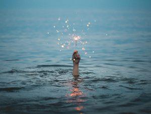 hand hold sparkler above the ocean